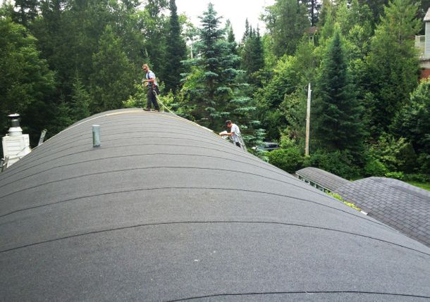 Two workers on an elastomeric membrane roof