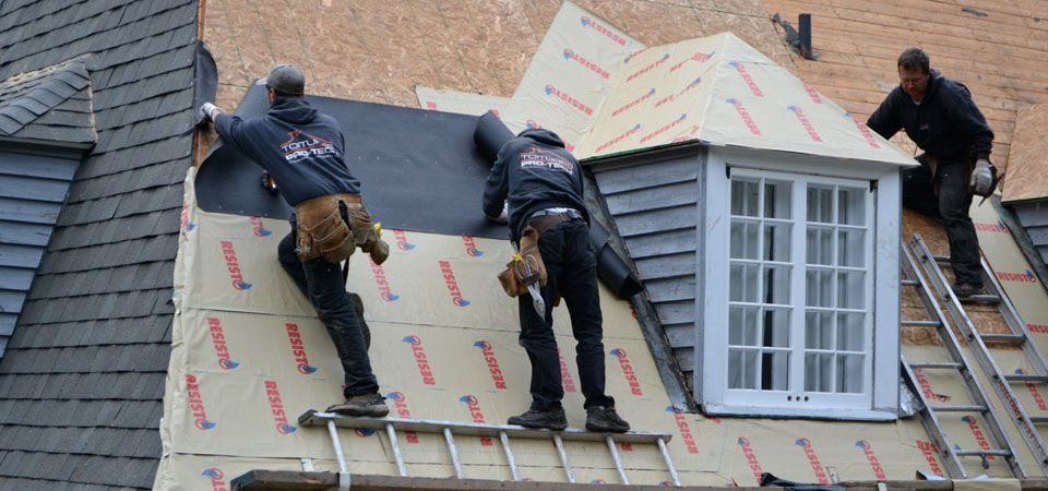 Three roofers at work